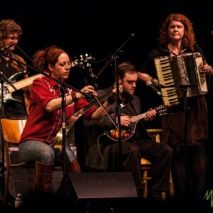 An Image Of 4 People Playing Instruments On Stage. 2 Have Long Red Hair, One Has Long Curly Hair, And The Other Has Short Hair. Our Focus Is Drawn To The Person In A Red Shirt And Playing A Long Unique Instrument.