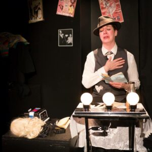An Image Of Charlie Portraying A Character On Stage. He Is Wearing A Tophat, A Vest On Top Of A Dress Shirt, And A Tie. He Has A Book In His Hand That Reads,