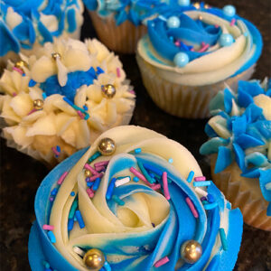 An Image Of Many Blue And White Cupcakes, Decorated With Sprinkles Of Blue, Pink, And Gold Colour.