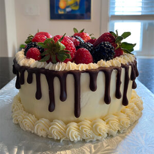An Image Of A Cylindrical Cake Topped With Strawberries And Blackberries. The Border Of The Cake Is Lined With Dripping Brown Icing On Top Of The Cream-coloured Base