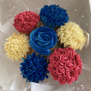An Image Of A Bouquet Of 7 Cupcakes. They Have Different Colours Of Icing: Blue, Cream, And Pink. The Icing Is Textured And Ornate.
