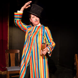 An Image Of Charlie On Stage, Wearing A Colourful Robe With Vertical Stripes And A Tophat. He Is Holding A Bottle Of A Brown Liquid. His Other Arm Is Outstretched Above His Head.