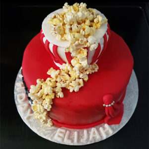A Two Tiered Red Cake, With The Top Tier Filled With Popcorn That Falls Down To The Bottom. The Border Of The Cake Reads,