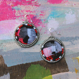 An Image Of 2 Circular Earrings. The Center Is Shiny Red And Black. They Are Lined With Small Silver Beads. An Image Of 2 Circular Earrings. The Center Is Shiny Red And Black. They Are Lined With Small Silver Beads.