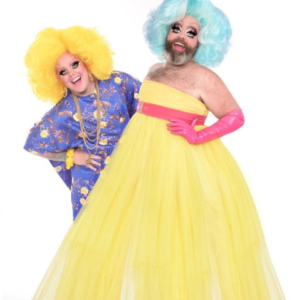 A Shot Of Fay & Fluffy In Front Of A White Background. Fay Is Wearing A Yellow Dress, With Pink Gloves And Blue Wig. Fluffy Is Behind With A Yellow Wig, And A Blue Floral Dress On.