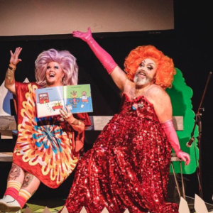An Image Of Fay & Fluffy On Stage. They Both Have Their Right Arm Stretched Out. Fluffy Is Holding A Book, Wearing A Light Purple Wig And A Multicoloured Dress. Fay Has An Orange Wig, Pink Gloves, And A Red Shimmering Dress On.