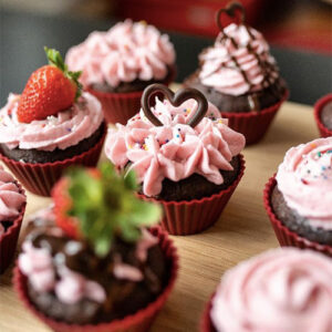 An Image Of Many Cupcakes With Pink Frosting. There Are Chocolate Hearts Or Strawberries On Most Of Them.