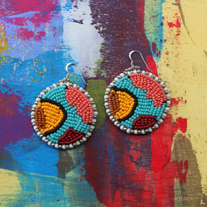 An Image Of 2 Circular Beaded Earrings. They Are Teal, Pink, Yellow, And Red, Lined With White And Silver Beads Around The Perimeter. The Background Is A Surface Of Abstract Paints.