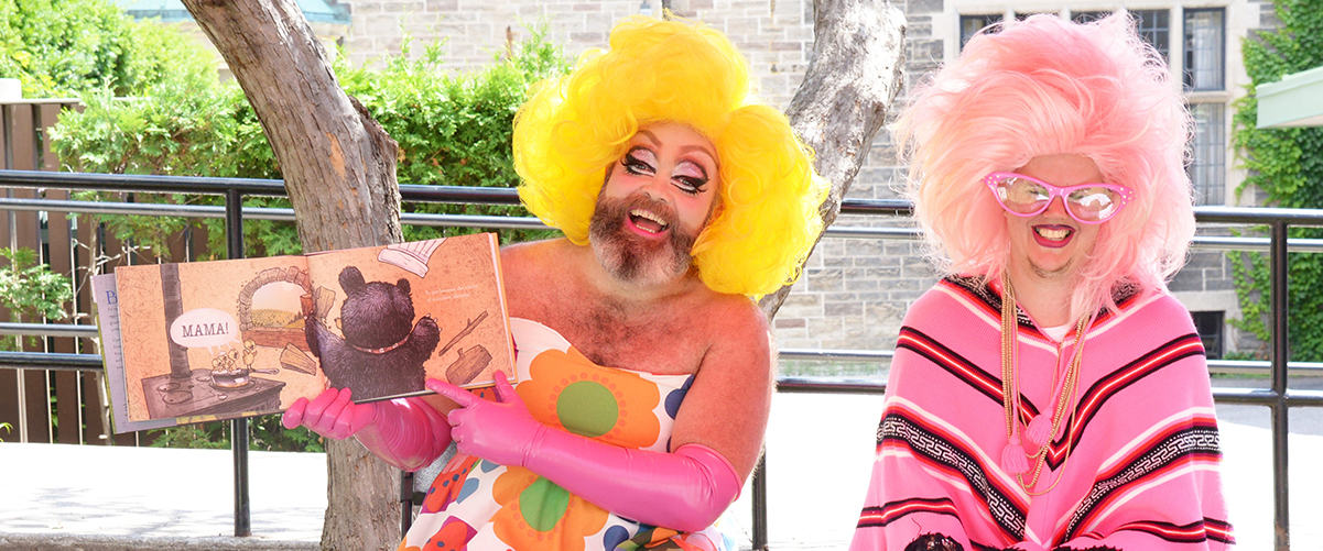 An image of Fay & Fluffy outside, sitting on chairs. Fay is holding up a picture book and has a yellow wig, pink gloves, and a floral dress on. Fluffy has a pink poncho, leggings lined with cats, a pink wig and pink glasses. They both have a large smile on their face.