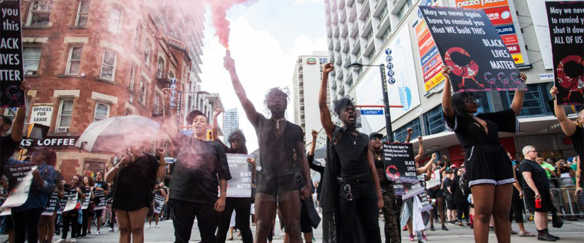 Demonstrators from Black Lives Matter Toronto at Toronto Pride on June 25, 2016. They stand in the middle of the street with arms and signs up to the sky.