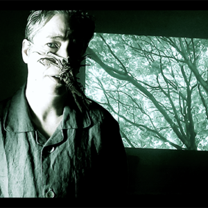 An Image Of Charlie With A Wooden Long Object Strapped To His Nose. The Background Shows A Screen Of Trees And Branches.