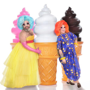 A Photo Of Fay & Fluffy In Front Of A White Background, Standing With 3 Large Ice Cream Cones. Fay Is Wearing A Blue Wig, With Pink Gloves, And A Yellow Dress. Fluffy Is Wearing An Orange Wig, A Blue Dress With Floral Print, And Yellow Bracelets. They Both Are Looking At The Camera With A Smile.
