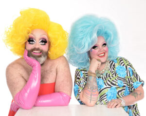 A headshot of Fay & Fluffy in front of a white background. Fay has a yellow wig on, pink gloves, and a red strapless dress on. Fluffy has a light blue wig and a patterned green, blue, white and blacktop . They both have their face resting on their right arm, with the other arm touching the table in front of them.