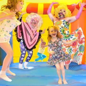 An Image Of 5 People Bouncing In A Yellow, Orange, And Blue Bounce Castle. 2 Of The People Are Fay & Fluffy, And The 3 Others Are Children. Everyone Looks Happy And Excited With Their Arms In The Air As They're Jumping. Fay Is Wearing A Yellow Wig, Pink Gloves, And A Floral Dress. Fluffy Is Wearing A Pink Poncho With Leggings Lined With Pictures Of Cats.