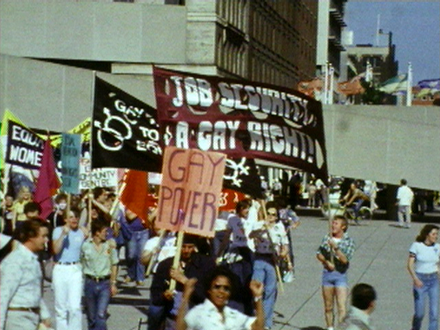 """A photo from the 60s or 70s of Pride Protestors holding various signs that read things like, """"Gay Power"""" and """"Job Security is a Gay Right!"""""""