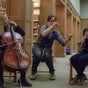 An Image Of Three People Playing Instruments In A Library. There Is A Cello, A Clarinet, And A Long Stringed Instrument With A Bow Being Played By Charlie.