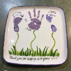 A White Square Plate With A Footprint, A Handprint, And Another Footprint Painted On It. The Prints Are In Purple, And Connect To Green, Painted Grass.