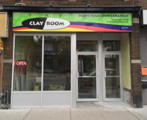 """An image of the storefront of The Clay Room. The sign on top of the store reads """"The Clay Room"""" in black and white, and """"Paint your own Ceramics"""" in purple. The background of the sign is green, with strips of purple, orange and yellow."""