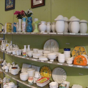 A Picture Of A Shelf In The Clay Room. The Shelves Display Many Kinds Of Ceramic Items To Be Painted. The Wall Colour Is Green-yellow.
