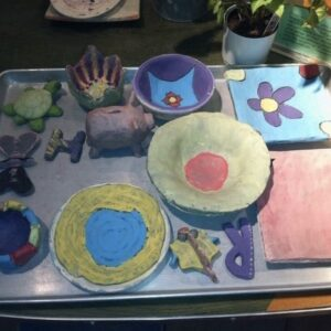 A Picture Of A Table Top With Different Ceramic Works In Progress. They Are Of Many Colours, And Include A Piggy Bank, A Turtle, Bowls And Plates.