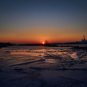 A Landscape Photo Of A Frozen Lake With The Sun Setting In The Horizon. The Sky Is A Gradient Of Blue To Orange. On The Right Side Of The Picture, We See The CN Tower And The Toronto Skyline.