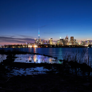 An Image Of The Lake In Front Of The Toronto Skyline. The Sky Is Dark Blue And Pink. The Buildings In The Distance Are Lit Up.