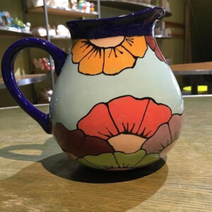 A Picture Of A Ceramic Jug, Painted In Light Blue, With Colourful Flowers. The Lip And Handle Of The Jug Is Deep Navy Blue.