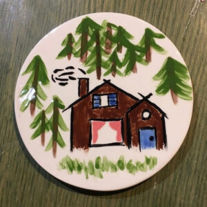 A Picture Of A Circular White Plate With A Brown House And Many Coniferous Trees Painted On It.