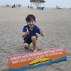 A Photo Of Lucas Walker On The Beach Behind A Sign. He Is Crouched Down With This Thumbs Up. The Sign In Front Of Him Reads,