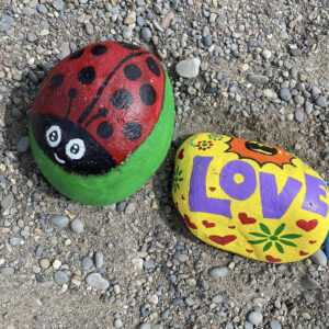 A Photo Of Two Painted Rocks. The Left One Is A Black And Red Ladybug With Eyes. The Right One Is Painted Yellow With Red Hears All Over And The Word