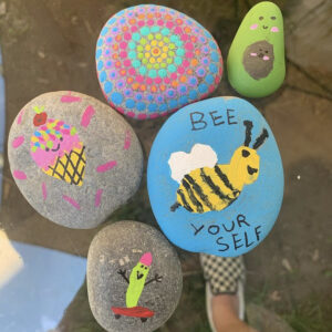A Photo Of 5 Different Painted Rocks. One Has An Ice Cream Cone With A Smile; Another Has A Painting Of A Bumble Bee That Says