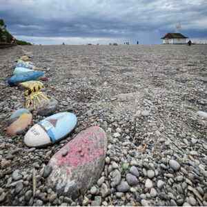 A Photo Of Woodbine Beach. In The Foreground Are Some Of The Painted Rocks In The Rock Snake. In The Background Is The Leuty Lifeguard Station. The Sky Is Cloudy And Dark Above The Beach.