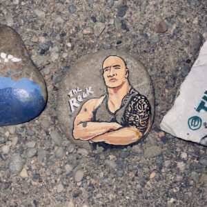 A Photo Of A Painted Rock. The Rock Has A Portrait Of Dwayne