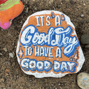A Photo Of A Painted Rock. The Rock Is Painted Orange With Blue And White Text On It That Reads,