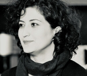 A black and white headshot of Mahsa Razavi. She has shoulder length dark hair, light skin tone, and a scarf on. She is looking away from the camera with a subtle smile.