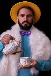 A portrait of Deivid. He has brown hair, with a beard and mustache. He is wearing a yellow brimmed hat, with a blue button up shirt, a purple bowtie, and a furry white scarf. He is holding an ornate teacup in his left hand, while pouring a liquid out of a teapot into it with his right hand. He is staring directly at the camera.