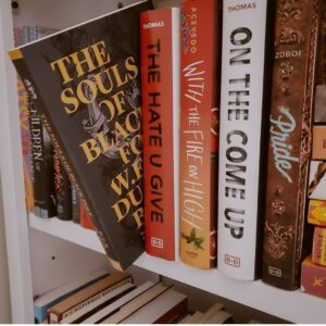 """An Image Of Many Books On A Shelf. One Is Pulled Out Halfway, Titled, """"The Souls Of Black Folk"""" By W.E.B. Du Bois."""