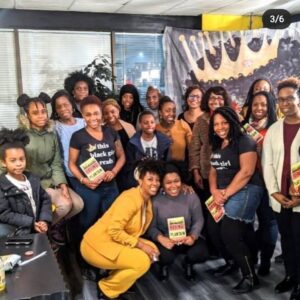 """A Picture Of Many People Smiling For The Camera. We See Two People With The Black T-shirt That Reads, """"this Black Girl Reads."""""""