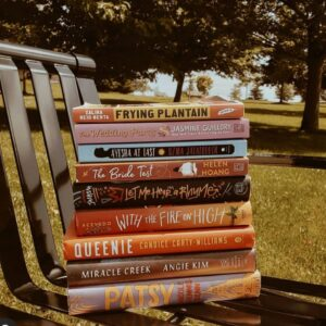 An Image Of A Stack Of 9 Books On A Park Bench. The Titles Include: Frying Plantain, The Wedding Party, Ayesha At Last, The Bride Test, Let Me Hear A Rhyme, With The Fire On High, Queenie, Miracle Creek, And Patsy.