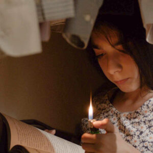 A Film Still Of A Young Child Holding A Lighter To Read A Book. She Appears To Be Under Hanging Clothes.