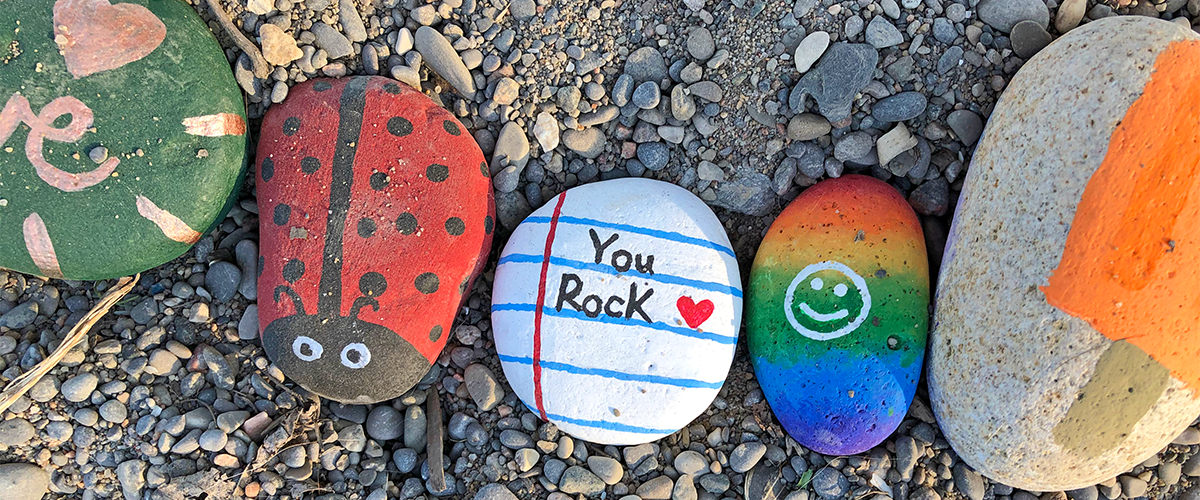 """A photo of some rocks in the woodbine beach rock snake. Visible is a rock painted as a black and red ladybudy, a rock that is painted white with blue lines meant to represent a lined sheet of white paper, and it reads """"You Rock"""" in black text; and a rainbow coloured rock with a white happy face over top."""