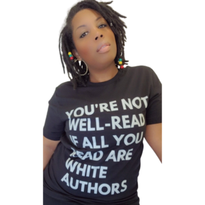 """A headshot of Lalaa Comrie. She has black shoulder length hair, dark skin tone, hoop earrings, and a black shirt that reads in white text, """"YOU'RE NOT WELL-READ IF ALL YOU READ ARE WHITE AUTHORS."""" She is looking directly into the camera."""