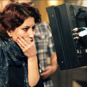 An Image Of Mahsa. She Has One Hand On Her Chin As She Is Looking At A Screen On Set.