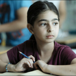A Bright Film Still Of A Young Child In A Red T Shirt, Holding A Pencil And Sitting At A Desk. She Is Looking To The Side.