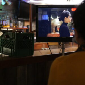 An Image That Has A Film Screen In Focus, With An Actress On It. Mahsa Is In Front, As We See The Back Of Her Head, Reviewing The Image.
