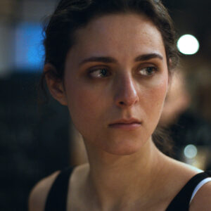 A Film Still Of An Actress With Dark Hair And Light Skin Tone. She Is Looking To The Side With A Pensive Look. The Background Is Out Of Focus.