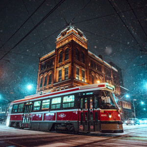 A Photograph Of A Red And White TTC Streetcar In Front Of The Broadview Hotel During Nighttime And Snowfall.