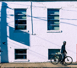 A Photograph Of Windows Of A Light Purple Building. There Are Shadows Of The Street Sign And Poles Cast On It. There Is Also A Person Walking A Bicycle In Front Of The Wall.
