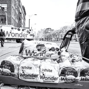A Black And White Photograph Of Crates Of White Wonder Bread Stacked On Top Of Eachother. In The Background, We See A Truck With