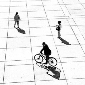 A Black And White Photograph Of A White Ground With Lines Running Through It To Make A Grid. The Shot Is Taken From A High Angle, Looking Down.There Are Three People On It: One Is On Bicycle, One Has Stopped And Is One Their One, And One Is Walking.